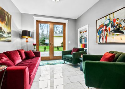 The family room area features colorful velvet seating flanking the French doors leading out to the yard. The marble tile continues through this space.