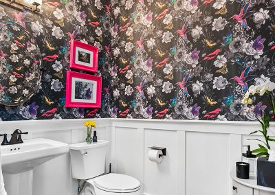A freshly remodeled bathroom with white, wood-paneled walls topped by colorful wallpaper featuring pink and blue birds and flowers.