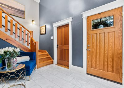 This marble-tiled entryway features classical Craftsman molding and a gorgeous blue velvet chair.