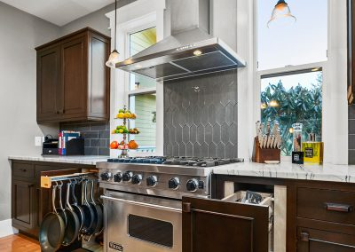 A newly remodeled kitchen with dark wood cabinets, grey marble countertops and classical Craftsman molding throughout..